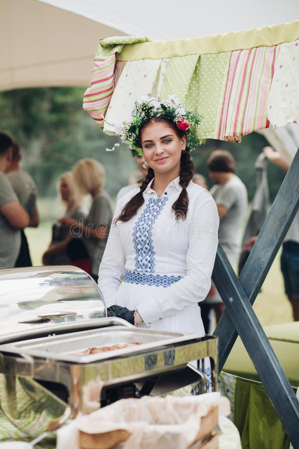Close-up waiter female wearing traditional Uzbek dress hand putting grilled piece of meat stock image