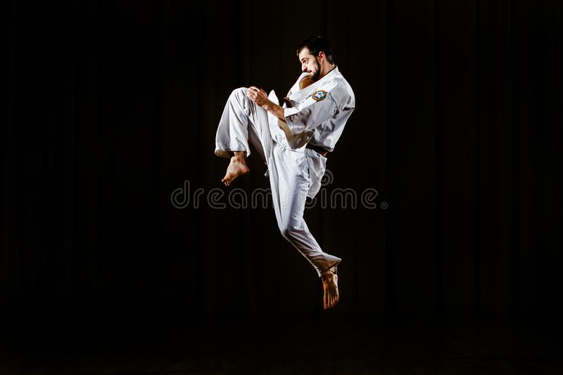 Young man jumping before kicking opponent. Self protection motion stock photography
