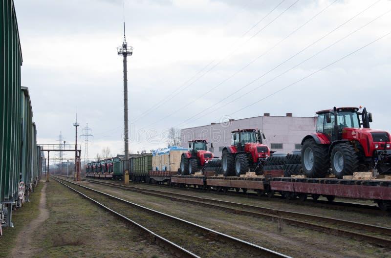 "New Three-door trolleybus by Belkommunmash and farm tractors ""Belarus`. Minsk, Belarus, Feb 18, 2020: New Three-door trolleybus by Belkommunmash and farm royalty free stock photography"