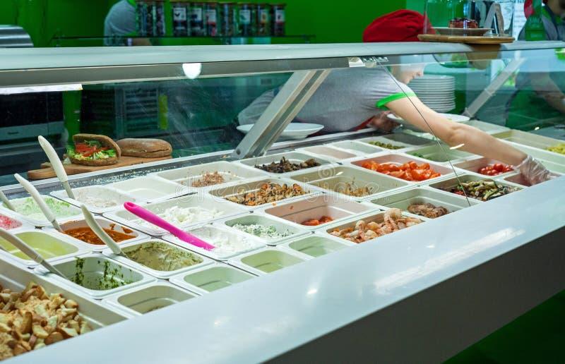 Minsk, Belarus - iune 17, 2017 : Un cuisinier prépare un plat avec assorti des ingrédients dans un ` de Salateira de ` de restaur image stock