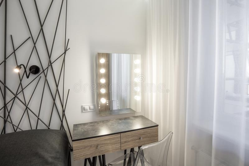 MINSK, BELARUS - January, 2019: bedside table with mirror and led lamps in Interior of the modern bedroom in loft flat in light royalty free stock images