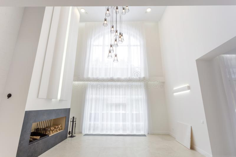 MINSK, BELARUS - JANUARY 2019: huge chandelier near fireplace for bright interior loft in front of a large panoramic window stock image