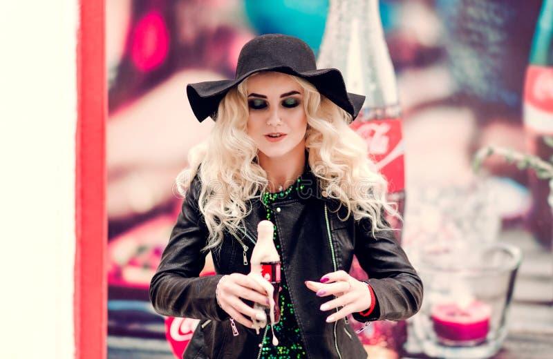 Minsk, Belarus - 30 janvier 2019 La fille adulte à la mode boit du Coca-Cola d'une bouteille photo stock