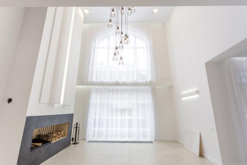 MINSK, BELARUS - JANVIER 2019 : lustre ?norme pr?s de chemin?e pour le grenier int?rieur lumineux devant une grande fen?tre panor image stock