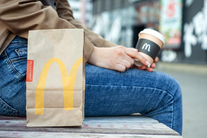 Minsk, Belarus, July 02, 2019: Paper bag McDonald`s on a bench next to a woman with paper cup of coffee in hand with McDonald`s lo royalty free stock photography