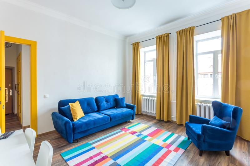 MINSK, BELARUS - March, 2019: retro bright interior of hipster flat apartments with blue sofa, yellow door and colored carpet royalty free stock images