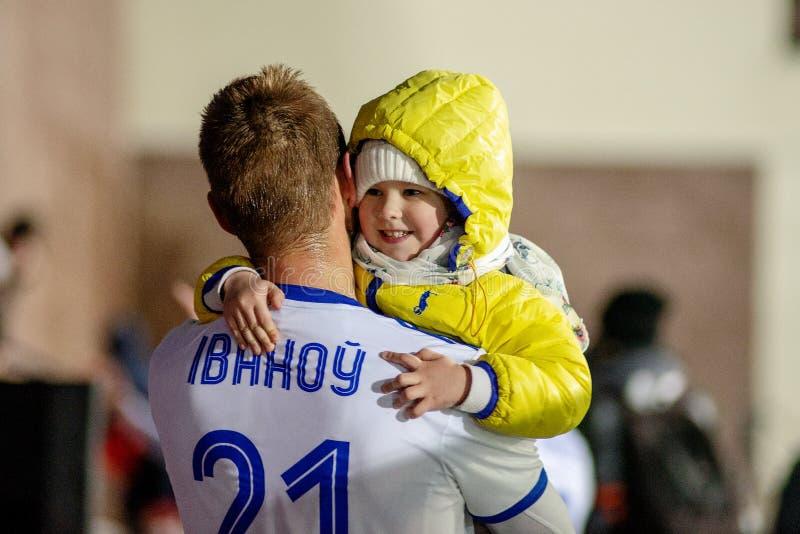 MINSK, BELARUS - 31 MARS 2018 : Le footballeur avec l'enfant célèbrent la victoire après le match de football biélorusse de ligue photo libre de droits