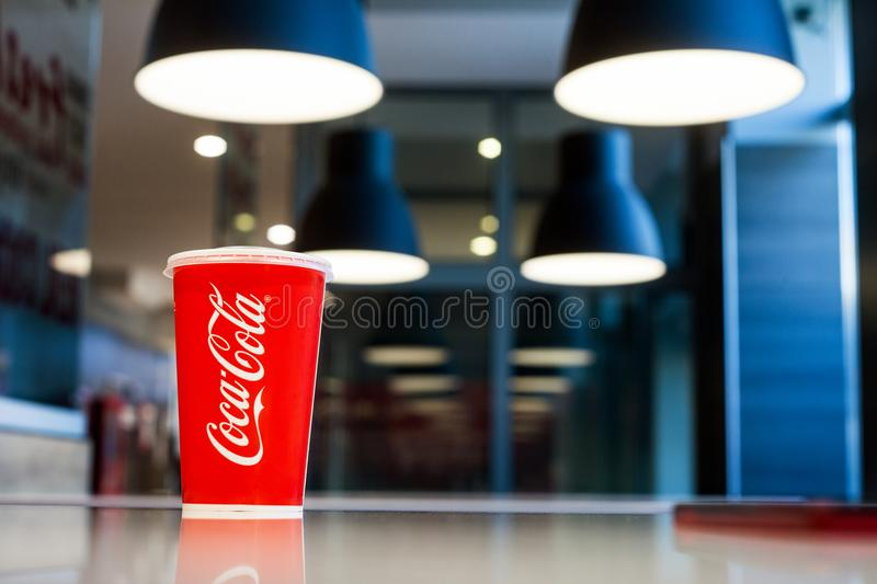 Minsk, Belarus, May 27, 2018: Paper cup of Coca-Cola on a table against background of lights of lamps above tables in cafe. stock photo