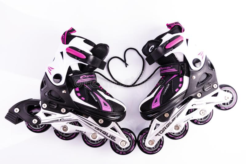 Minsk, Belarus, October 20, 2019. Black and white rollers with pink on a white background. Shoelaces tied in the shape of a heart stock image