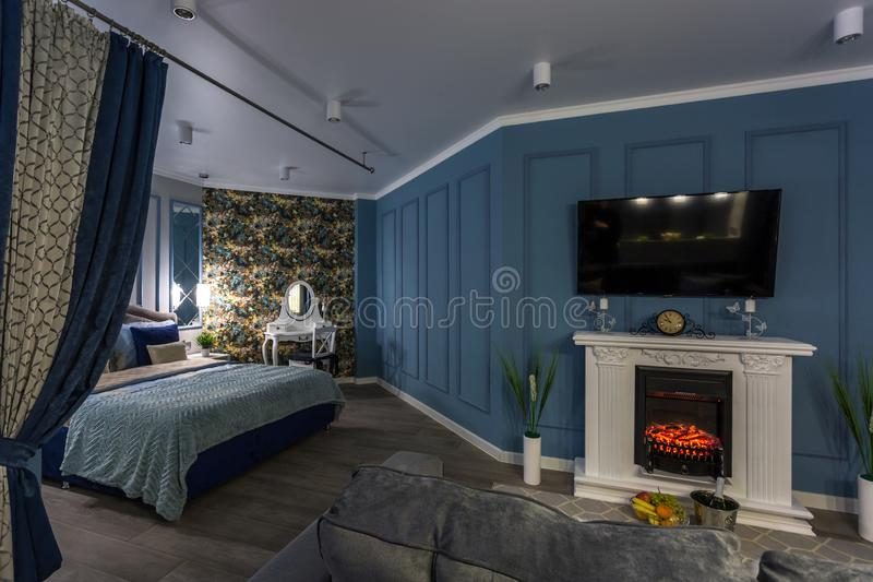 MINSK, BELARUS - SEPTEMBER, 2019: Interior of the modern luxure intimate bedroom with fireplace in studio apartments.  stock photo