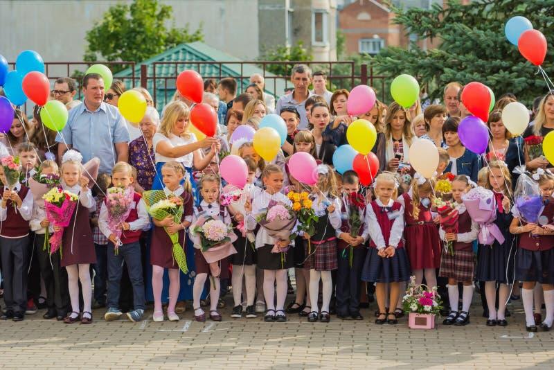 Minsk, Bielorrússia - 1º de setembro de 2018 Primeiro-graduadores com as flores fotografia de stock