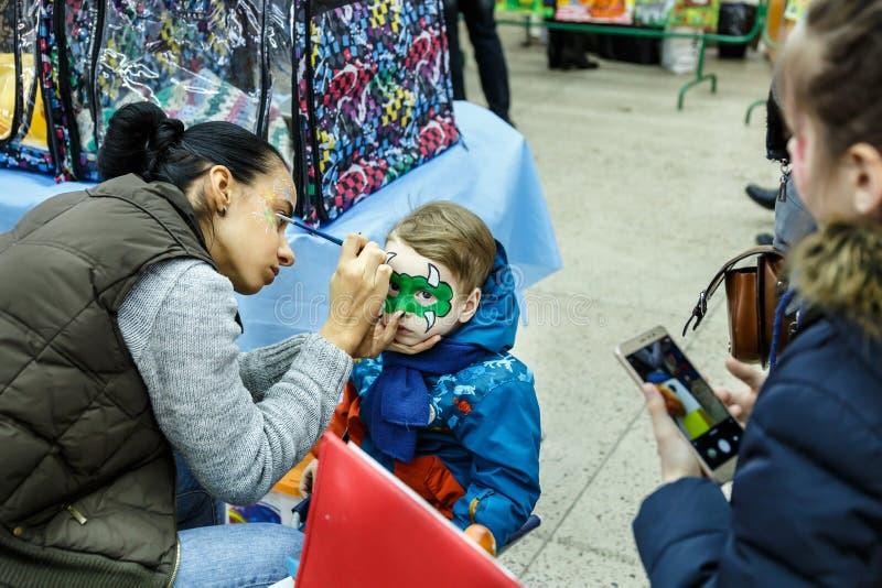 MINSK, BIELORRÚSSIA - 12 DE FEVEREIRO DE 2017: a mulher obtém a exposição do animal do menino do aquamakeup fotografia de stock royalty free
