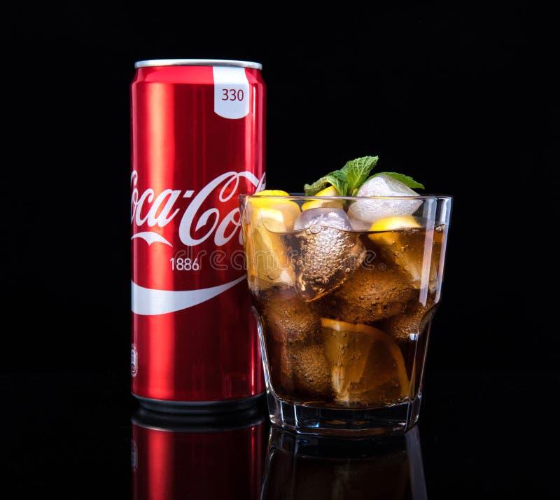 MINSK, BIELORRÚSSIA - 5 DE JANEIRO DE 2017: A foto editorial pode e vidro de Coca-Cola com gelo no fundo escuro Coca-Cola é foto de stock