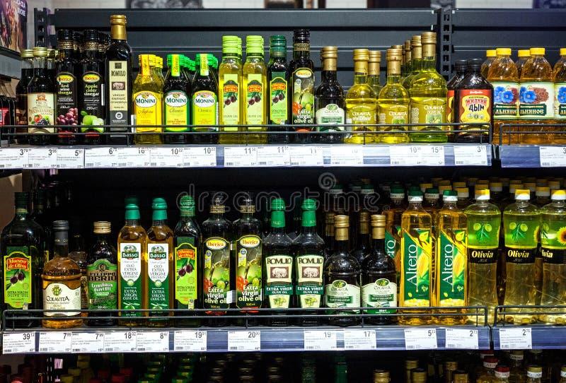 Minsk, Bielorrússia, o 1º de setembro de 2018: Óleos diferentes na montra no supermercado Azeitona, milho, girassol e o outro óle foto de stock royalty free