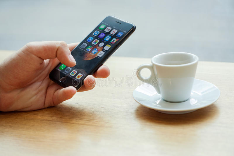Minsk, Bielorrússia, o 17 de julho de 2017: Entregue usando Iphone com ícones móveis da aplicação com uma xícara de café na tabel imagens de stock royalty free