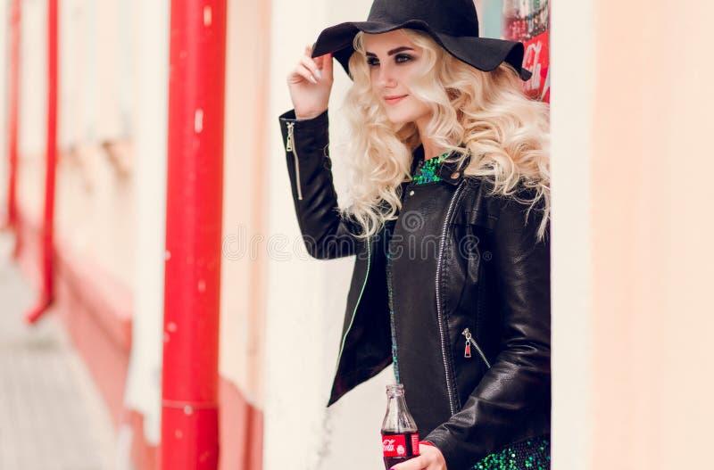 Minsk, Bielorr?ssia - 30 de janeiro de 2019 Menina adulta elegante com uma garrafa da coca-cola em suas mãos imagens de stock royalty free