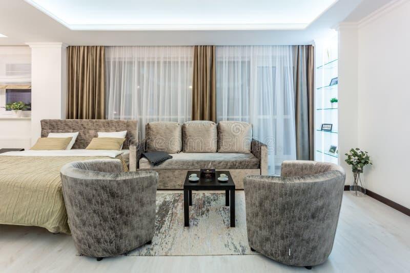 MINSK, BIELORR?SSIA - em janeiro de 2019: apartamentos lisos do s?t?o interior do sal?o do luxure com sof? e poltronas da tev? foto de stock