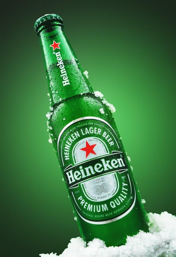 MINSK, BIELORRUSIA - 26 DE MARZO DE 2019: Botella fría de Heineken Lager Beer con hielo sobre fondo verde Heineken es fotos de archivo libres de regalías