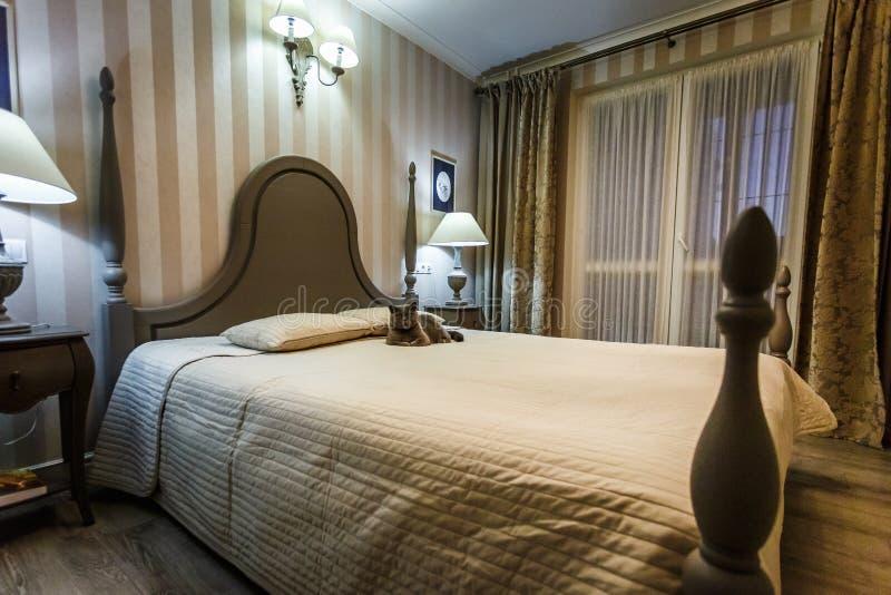 MINSK, BIELORUSSIA - febbraio 2019: Interno della camera da letto moderna nel piano del sottotetto in appartamenti costosi con il immagine stock libera da diritti