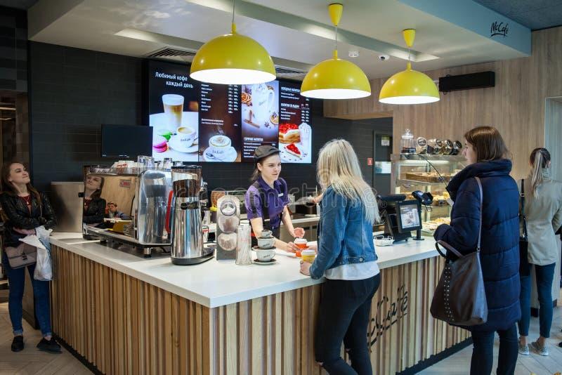Minsk, Bielorussia, il 24 aprile 2018: Interno di McCafe nel ristorante del ` s di McDonald Il barista dà l'ordine al cliente fotografie stock