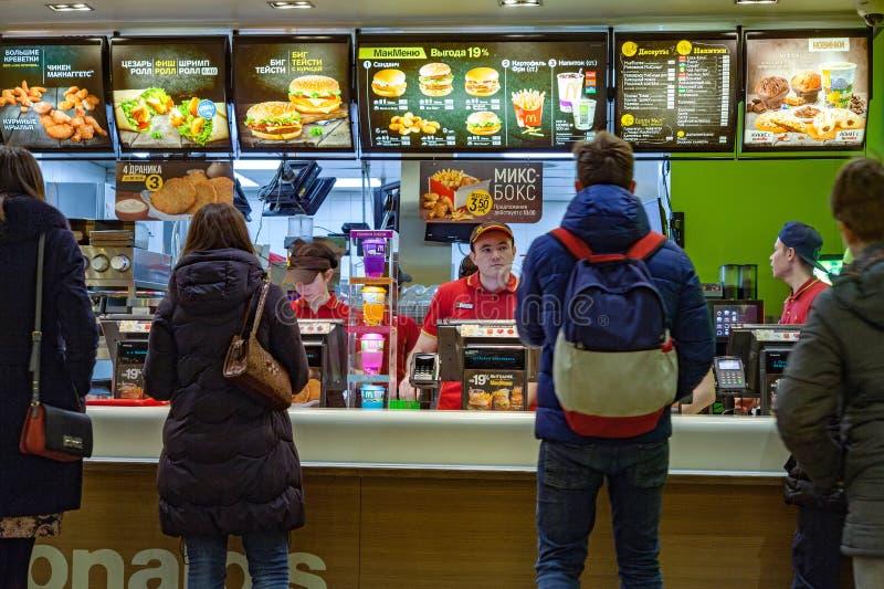 Minsk, Bielorussia, l'8 gennaio 2018: Alimento di ordine della gente in un ristorante del ` s di McDonald fotografia stock