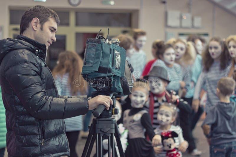 Minsk, Bielorussia - 11 novembre 2016: Il video operatore rimuove i bambini alla macchina fotografica fotografie stock libere da diritti