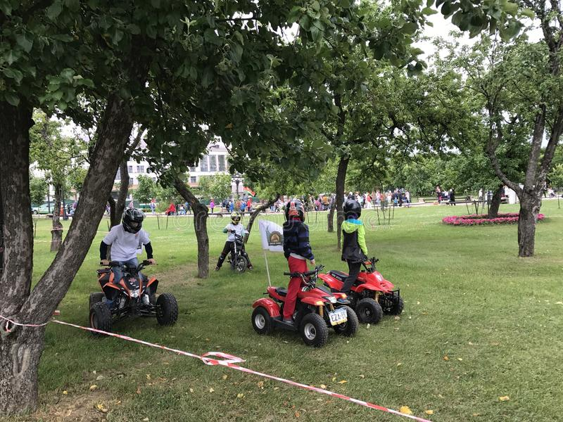 MINSK, MINSK, BELARUS, JULY 3, 2017; City holiday, Independence Day. Entertainment in the city park. Children ride on quad bikes stock photography
