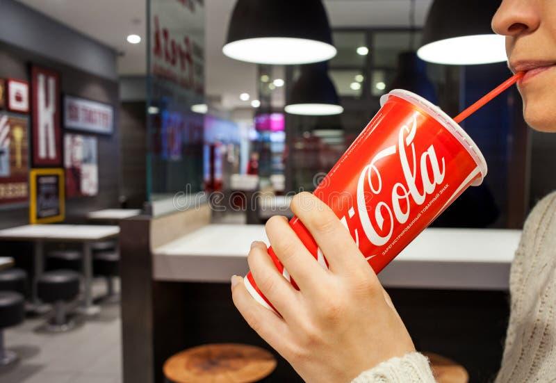 MINSK, październik 30, 2017: koka-kola miękki napój Kobieta pije koka-koli na kawiarni obrazy royalty free
