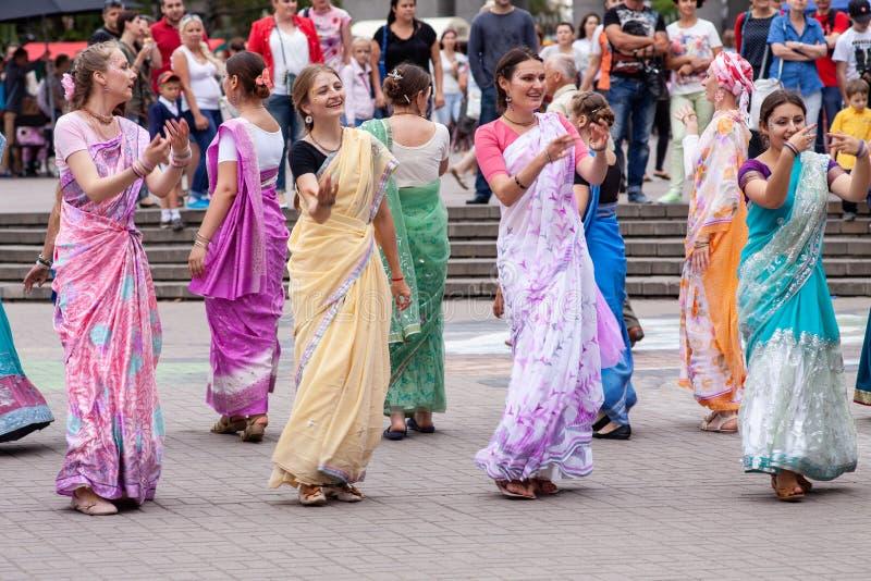 Minsk Vitryssland - august 16, 2014: L?rjungar av dansen f?r hareKrishna r?relse och skanderab?ner p? stadsgatan arkivfoton