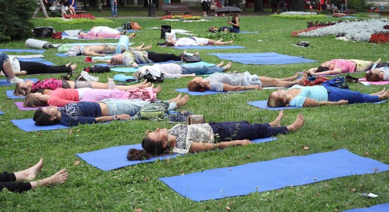 Minsk Vitryssland - august 16, 2014: Praktiserande yoga för folk i parkera royaltyfri bild