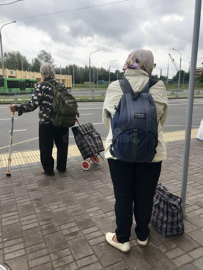 MINSK MINSK, VITRYSSLAND 7 JULI 2019, en äldre kvinna går tillbaka från hennes sommarhus Bak dem har de tunga ryggsäckar, i royaltyfri bild