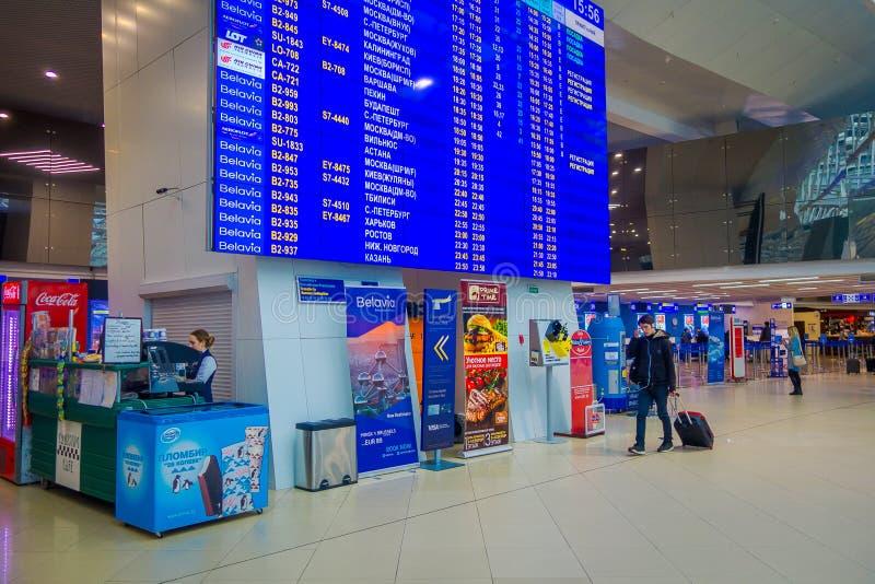 MINSK, WEISSRUSSLAND - 1. MAI 2018: Nicht identifizierte Leute, die unter einen enormen Abfahrtschirm mit Ankünften und Zeitplan  stockfotografie