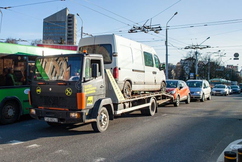 Minsk, Wit-Rusland, 4 April, 2018: De slepenvrachtwagen vervoert een defecte minibus stock afbeelding