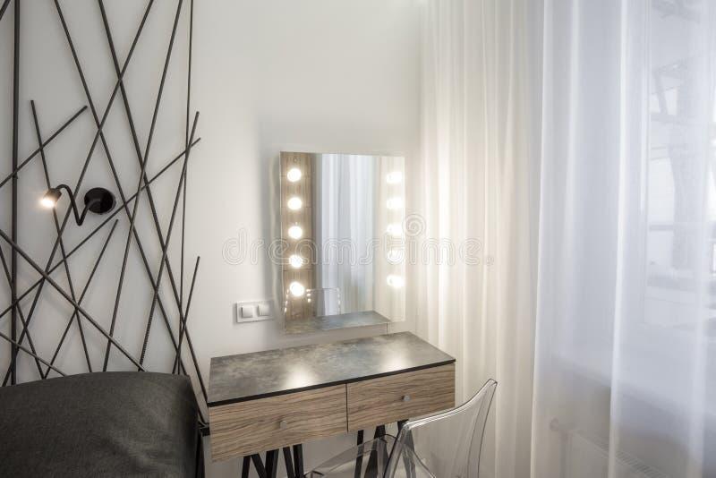 MINSK, WIT-RUSLAND - Januari, 2019: bedlijst met spiegel en geleide lampen in Binnenland van de moderne slaapkamer in zolder vlak royalty-vrije stock afbeeldingen