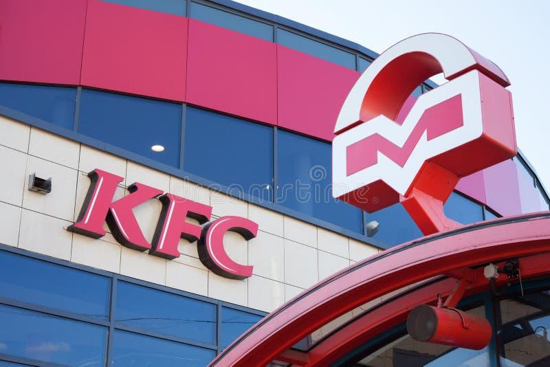 Minsk, Wit-Rusland, 10 juli, 2017: Het snelle voedselrestaurant van KFC naast ingang aan metro Emblemen van KFS en Metro van Mins royalty-vrije stock foto