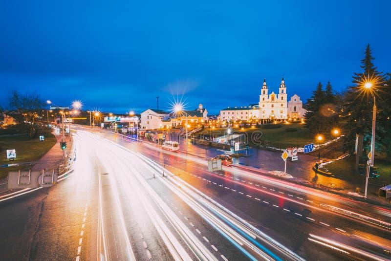 Minsk, Wit-Rusland Nachtverkeer op Verlichte Straat en Kathedraal van Heilige Geest in Minsk royalty-vrije stock foto's