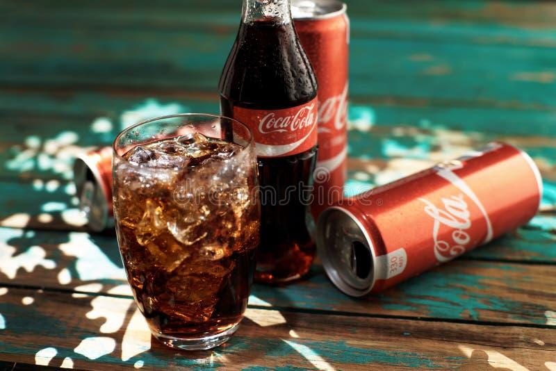 MINSK, 25 WITRUSSISCH-AUGUSTUS, 2016 Kan en een glas van bevroren Coca-Cola op een houten lijst royalty-vrije stock foto