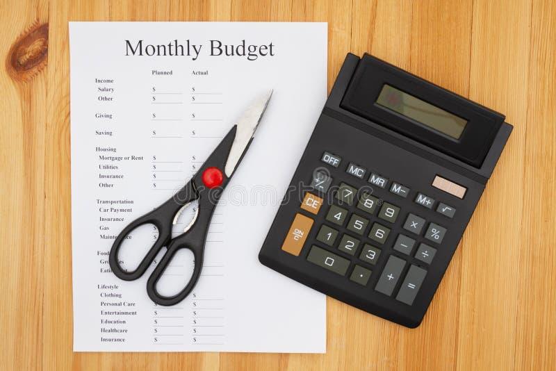 Minska din månadsbudget med en räknare och sax royaltyfria foton