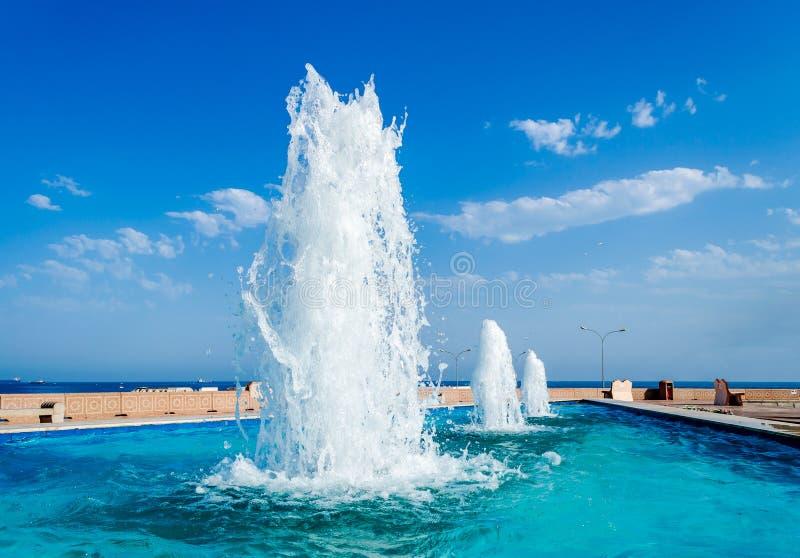 Minska perspektiv av vattenspringbrunnar mot en blå himmel royaltyfria foton