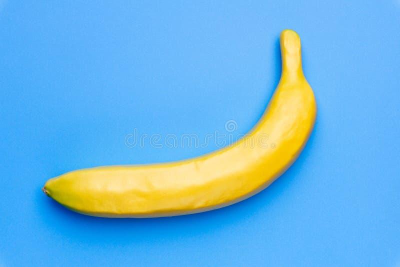 Minsta begreppsbananfrukt på kulör blå pastellfärgad bakgrund arkivfoto