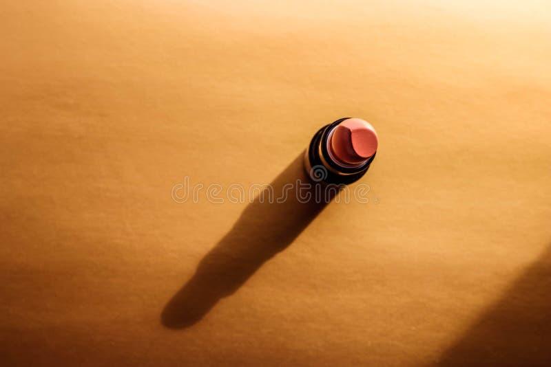 Minsta utgör begreppet med ensam näck läppstift på guld- bakgrund med skugga fotografering för bildbyråer