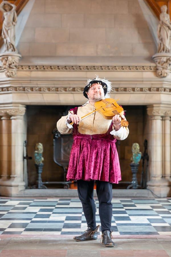 Minstrel im mittelalterlichen Kostüm, das eine Violine in Edinburgh-Schloss spielt stockbilder