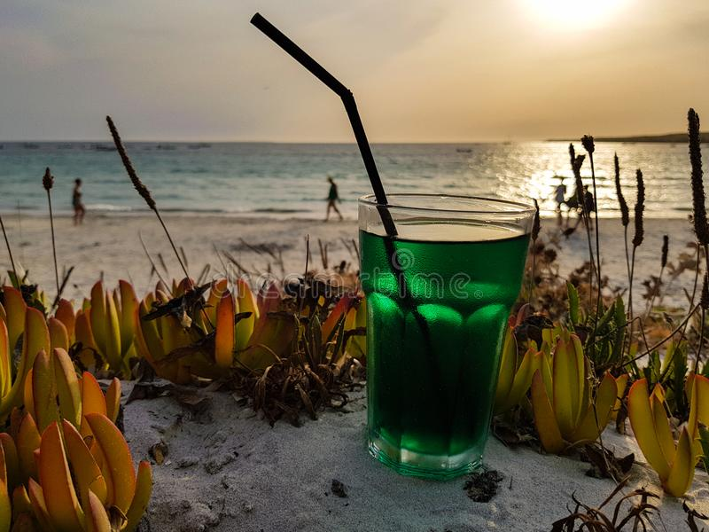 Summer cocktail on the beach at sunset. Mint-based cocktail ready to be sipped by the sea royalty free stock photography