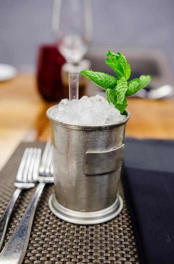 Mint and burbon cocktail. Mint Julep with ice in a special metallic container royalty free stock images
