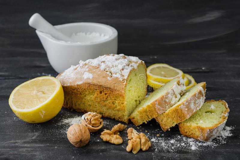 Mint cake on black surface with lemon, nuts, powdered sugar stock photo