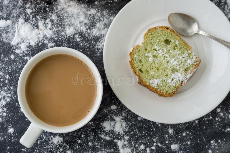 Mint cake sprinkled with powdered sugar on dark surface with coffee cup, top view stock photo