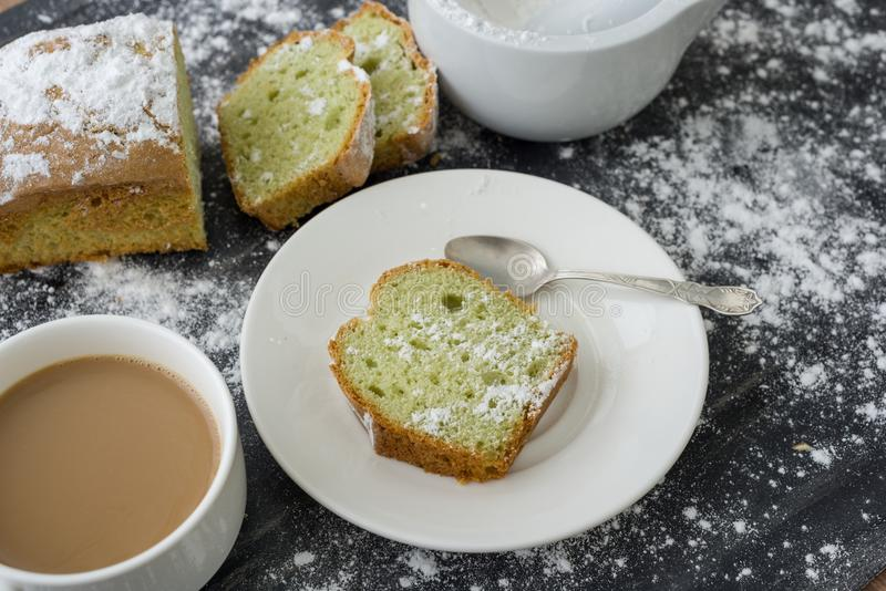Mint cake sprinkled with powdered sugar on dark surface with cup of coffee royalty free stock photos