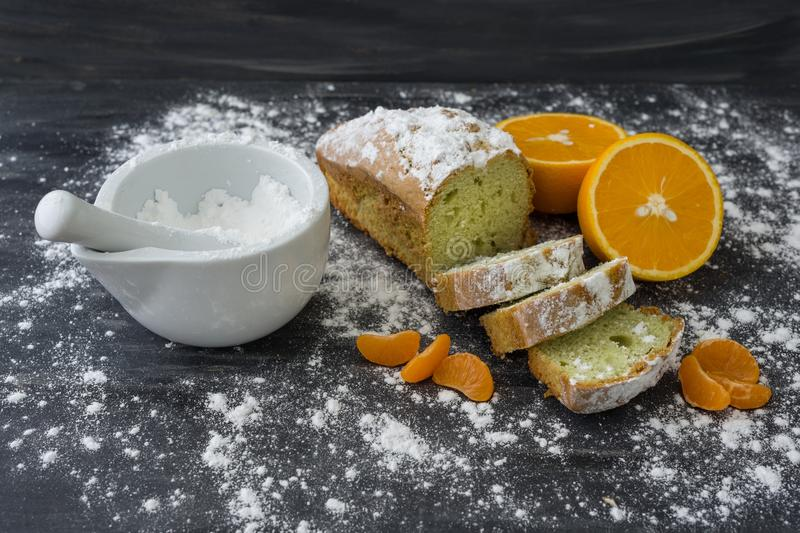 Mint cake sprinkled with powdered sugar on dark surface with fresh oranges mandarins royalty free stock photos