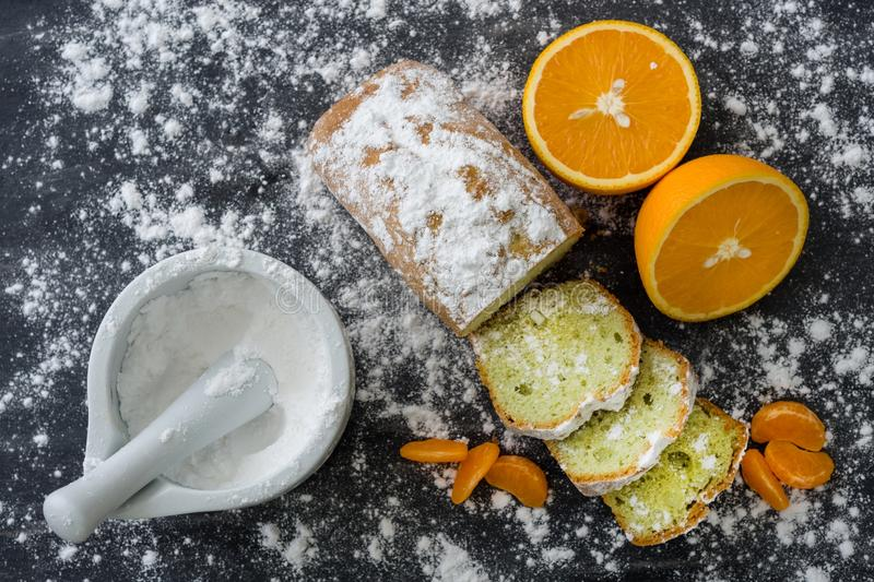 Mint cake sprinkled with powdered sugar on dark surface with fresh oranges mandarins. royalty free stock image
