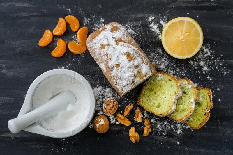 Mint cake sprinkled with powdered sugar on dark surface with fresh oranges mandarins stock photo